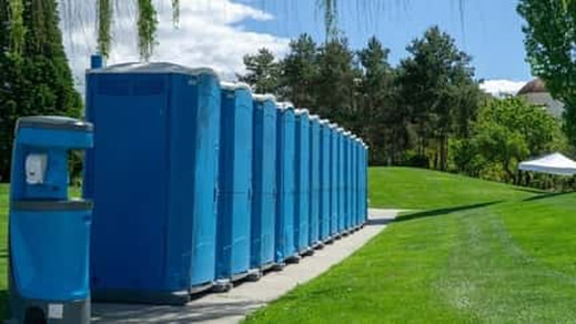 A picture of portable toilets in a parking lot for a sporting event.